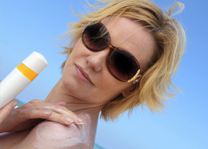 Woman applying sun screen