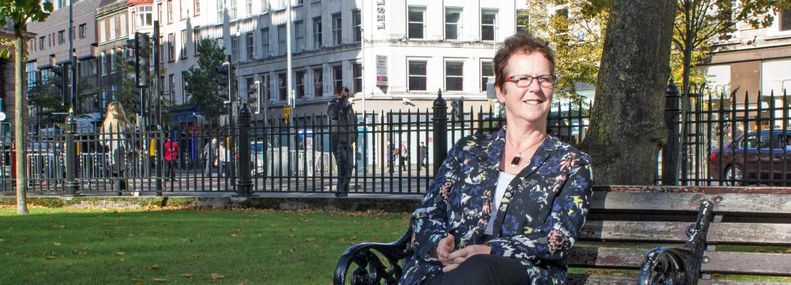 Linda Giles sitting on a bench outside Belfast City Hall